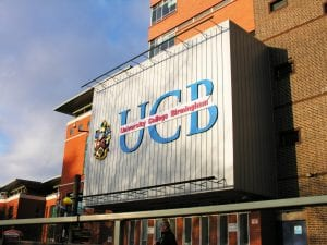 Outside view and close-up photograph of UCB Summer Row logo and signage.